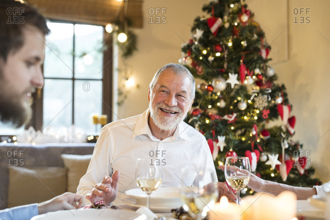 Smiling senior man looking at adult son at Christmas dinner table