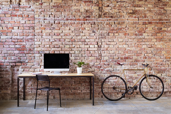 Workspace and bicycle at brick wall in office