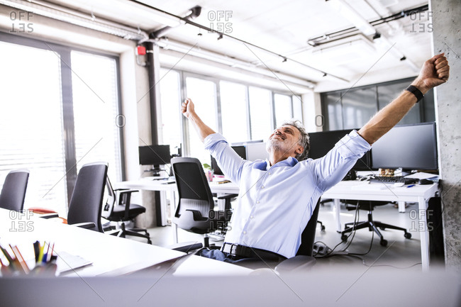 Happy mature businessman sitting at desk in office raising his arms