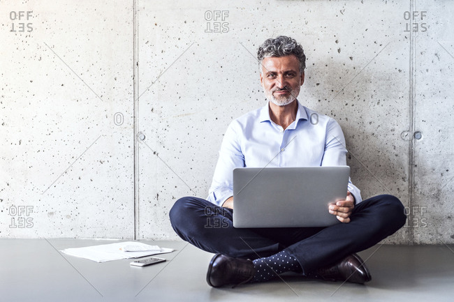 Portrait of confident mature businessman sitting on the floor using laptop