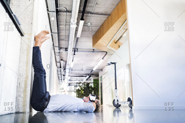 Barefoot mature businessman lying on floor in office wearing VR glasses