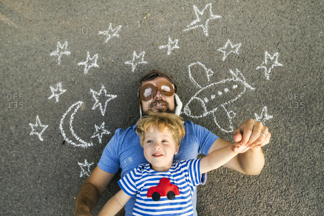 Portrait of mature man wearing pilot hat and his little son lying on asphalt painted with airplane- moon and stars
