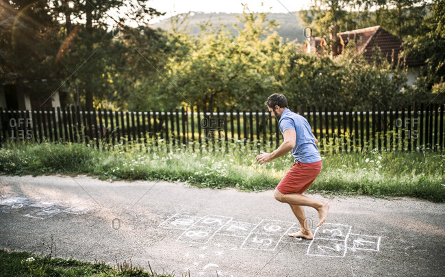 Man playing hopscotch with naked feet