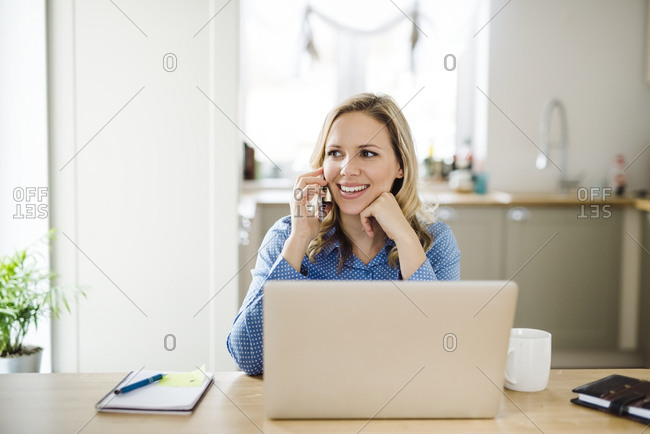 Smiling woman with laptop and cell phone working at home