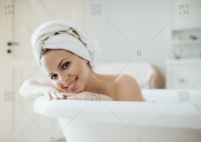 Portrait of smiling woman with towel around her head taking a bath at home