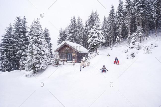 Austria- Altenmarkt-Zauchensee- family tobogganing at wooden house at Christmas time