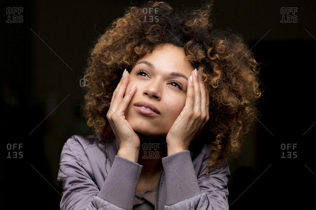Portrait of daydreaming woman in front of black background