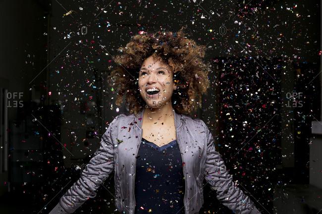 Confetti falling on amazed woman