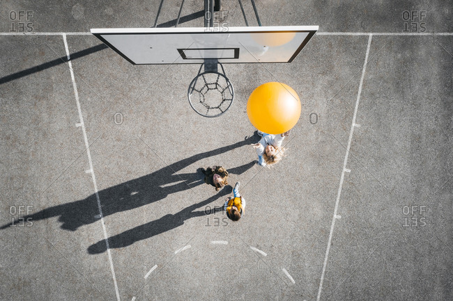 Austria- Aerial view of basketball field- mother and children playing basketball with big ball