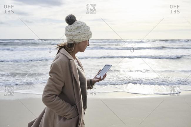Spain- Menorca- senior woman walking on the beach in winter reading E-Book
