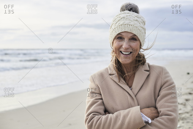 Spain- Menorca- portrait of happy senior woman on the beach in winter