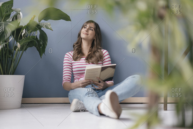 Woman sitting on ground in her new home- reading a book- surrounded by plants