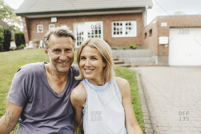 Portrait of smiling mature couple sitting in garden of their home