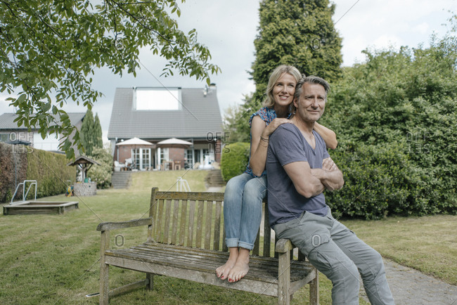 Smiling mature couple in garden of their home