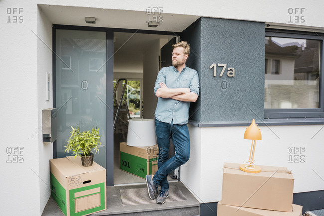 Man standing at house entrance surrounded by cardboard boxes