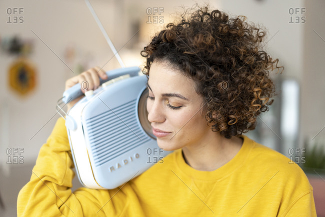 Woman listening to music with portable radio at home