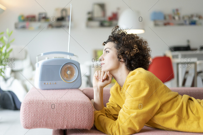 Woman lying on couch listening to music with portable radio at home