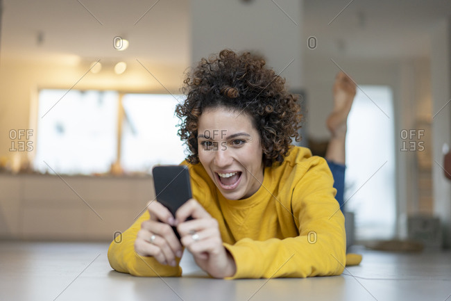 Excited woman lying on the floor at home using cell phone