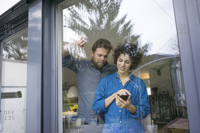 Couple behind window at home using cell phone