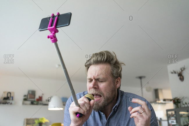 Man at home singing into microphone attached to a selfie stick