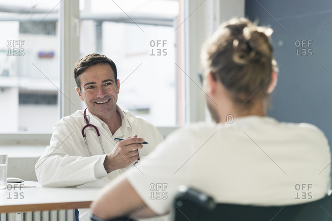Smiling doctor talking to patient in wheelchair in medical practice