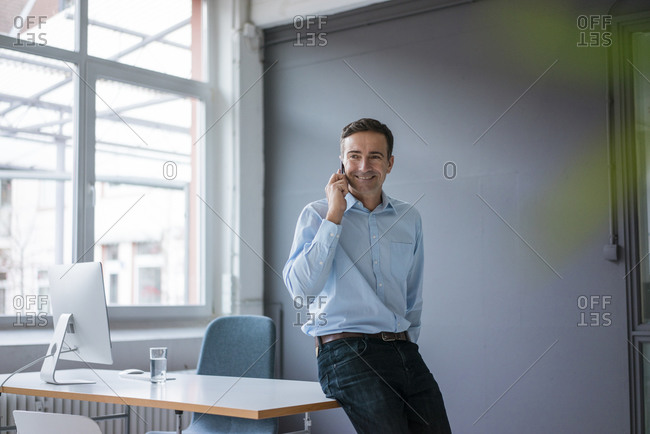 Smiling businessman on cell phone in the office