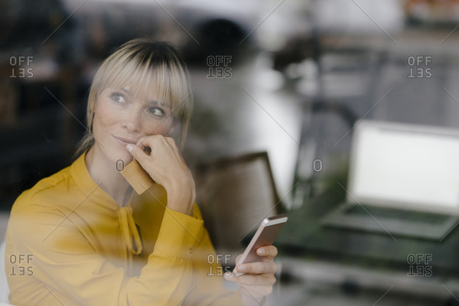 Blond businesswoman sitting at window- doing a payment with smartphone and credit card