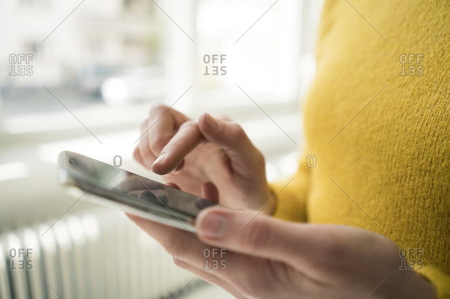 Woman in yellow pullover- using smartphone