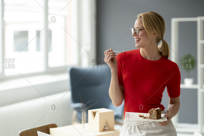 Happy young woman eating a piece of cake in office