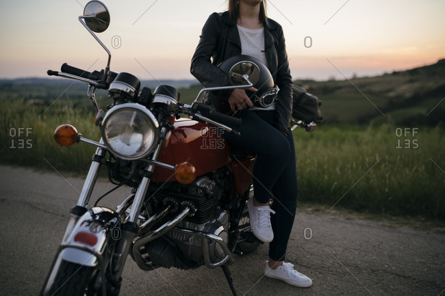 Crop shot of young woman with vintage motorbike on country road at sunset- Tuscany- Italy