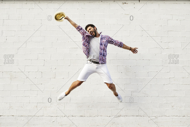 Happy man jumping mid-air in front of white wall
