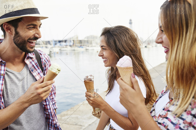 Three happy friends holding ice cream cones