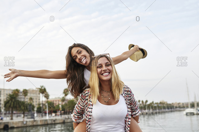 Spain- Barcelona- young woman giving her friend a piggyback ride