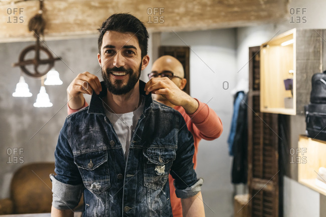 Handsome man trying on new denim jacket with stylist in modern boutique