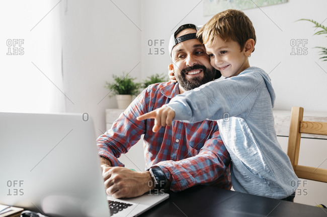 Father and son using laptop together
