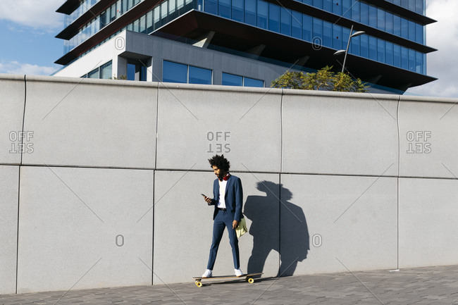 Spain- Barcelona- young businessman riding skateboard and using cell phone in the city