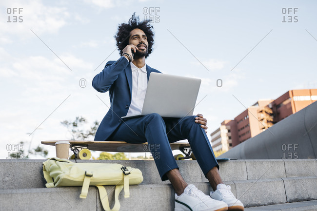 Spain- Barcelona- young businessman sitting outdoors in the city using cell phone and laptop