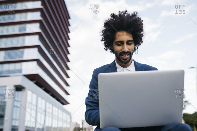 Spain- Barcelona- smiling young businessman sitting outdoors in the city working on laptop
