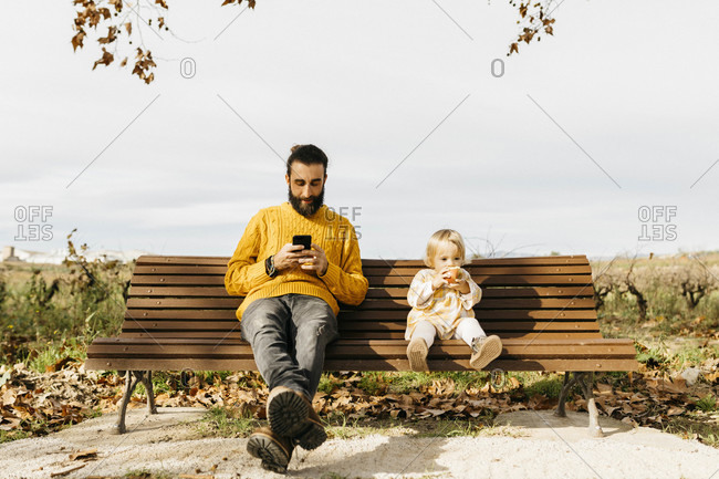 Father and daughter sitting on a bench in the park in autumn- father using smartphone- daughter eating an apple