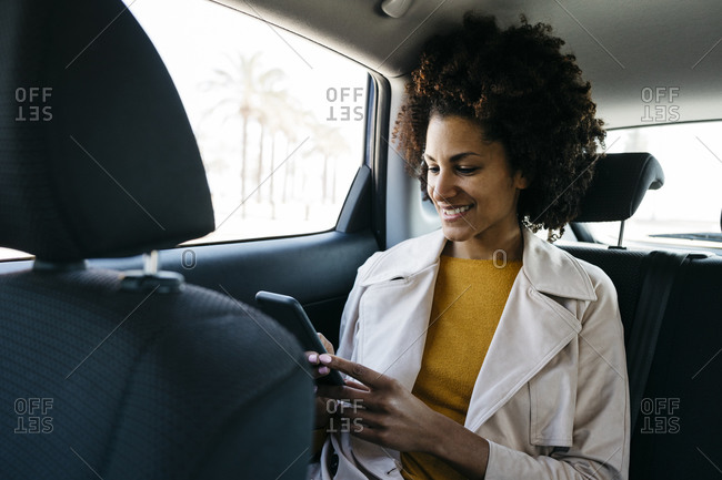 Smiling woman sitting in back seat of a car using cell phone