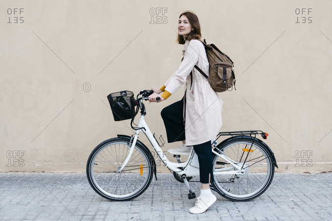 Woman with e-bike at a wall