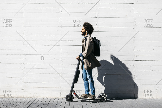 Man with backpack on E-Scooter