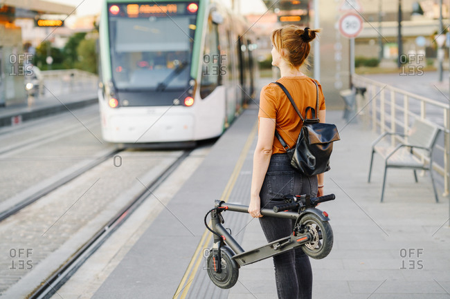 Back view of woman with backpack and folded electric scooter waiting at tram stop