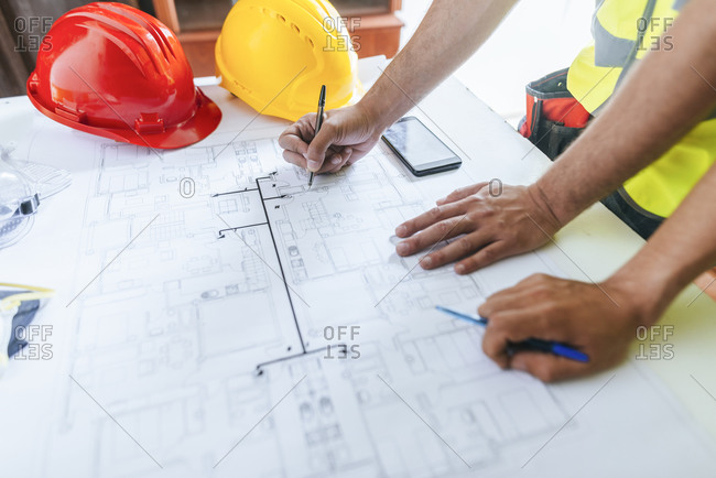 Close-up of workers hands working on construction plan