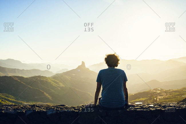 Spain- Canary Islands- Gran Canaria- back view of man watching mountain landscape