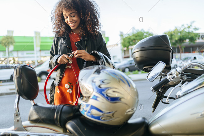 Smiling young woman removing safety lock from her motorcycle