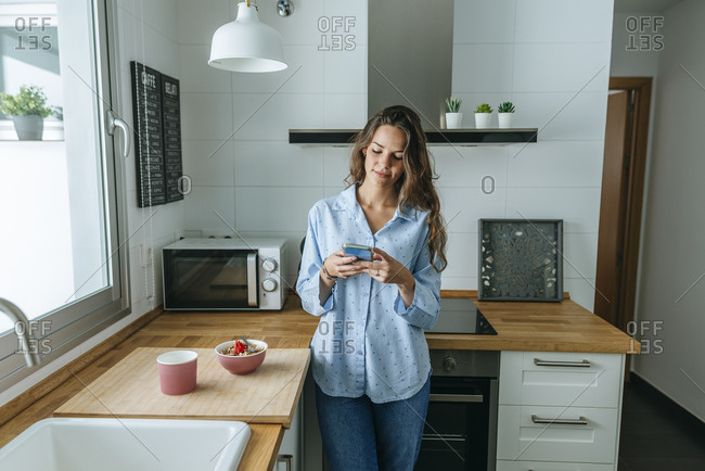 Young woman wearing pajama in kitchen at home using cell phone