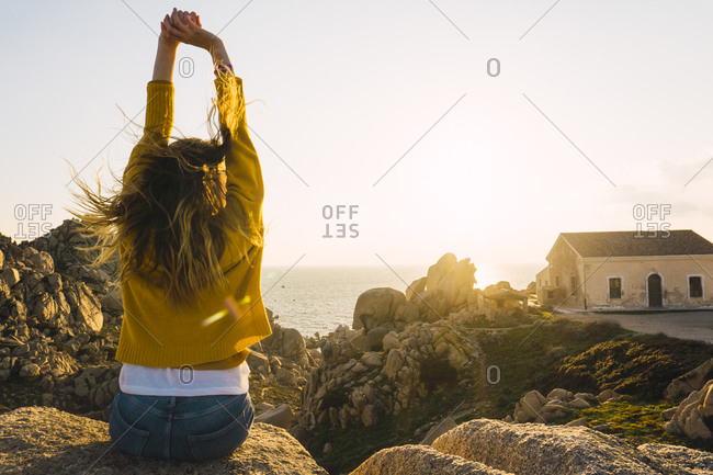 Italy- Sardinia- woman on a hiking trip sitting on rock at the coast raising her arms