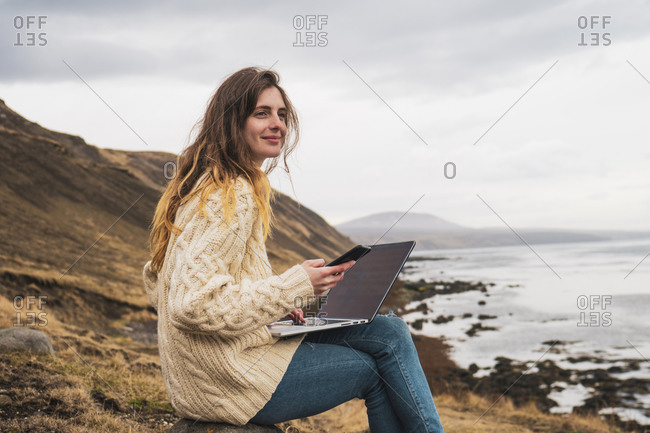 Iceland- woman using laptop and cell phone at the coast
