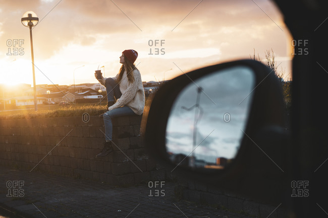 Iceland- young woman with coffee to go at sunset- wing mirror